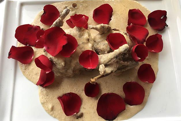 """Plato """"Como agua para chocolate"""", codornices rellenas, bañadas en mole de piñón blanco y rosa, con chocolate blanco en el bello restaurante Ciudad Sagrada. Foto © Silvia Lucero"""